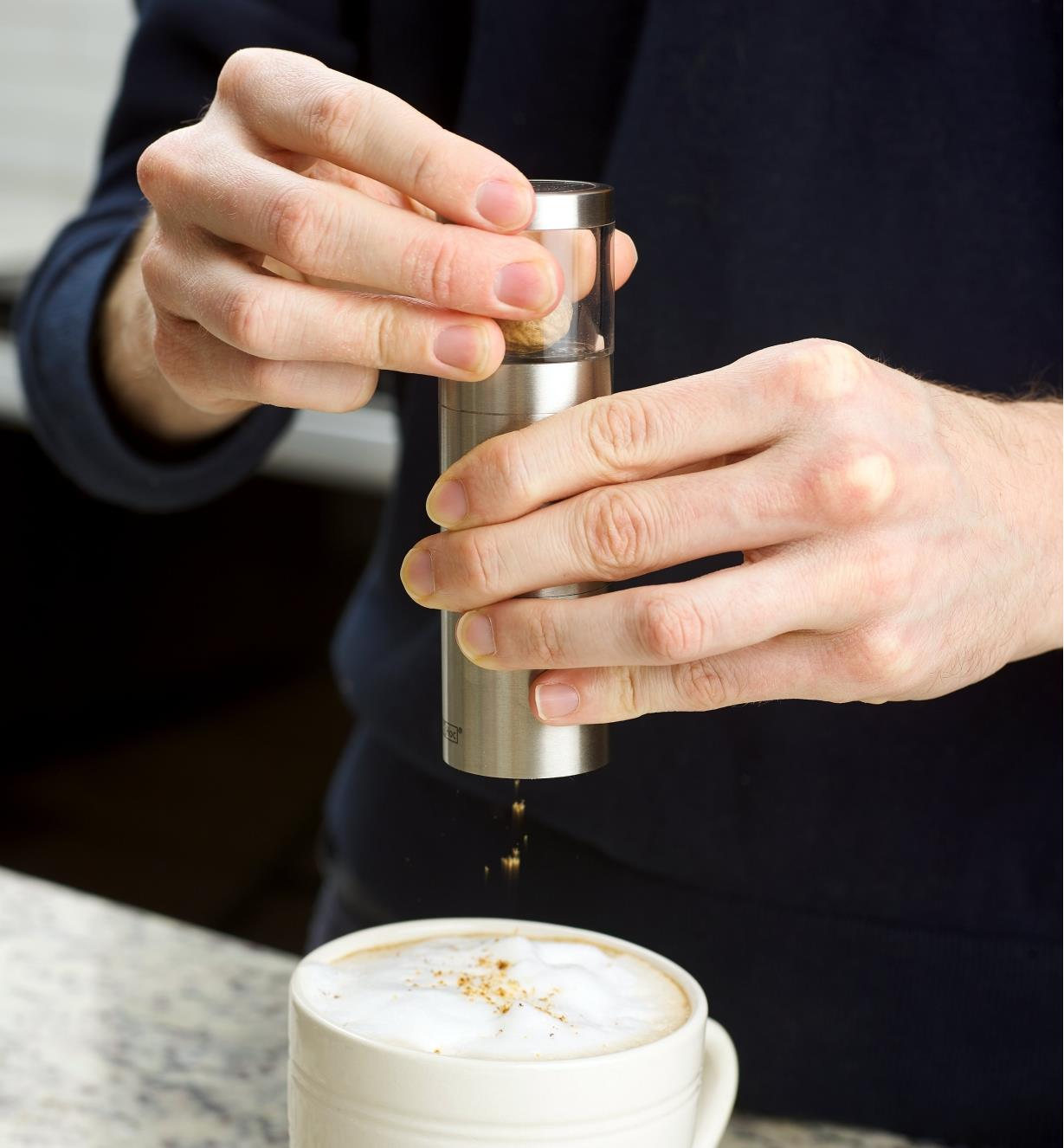 Using the nutmeg grinder over a mug of coffee