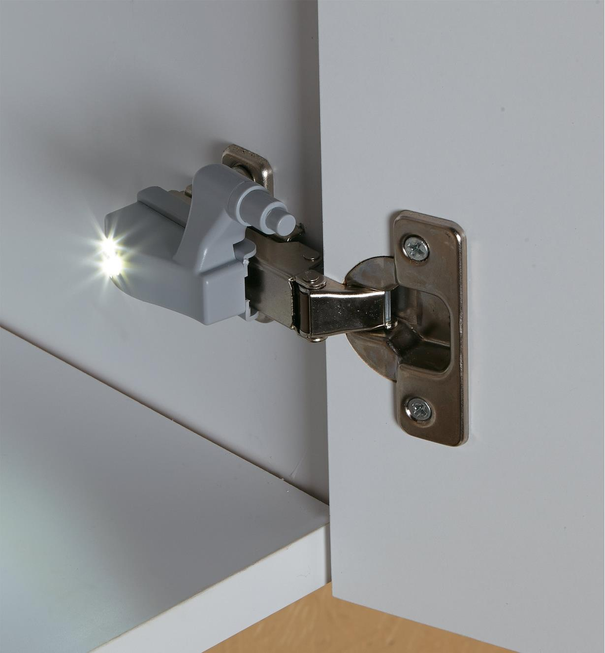 Wireless Hinge LED mounted on a hinge inside a cabinet