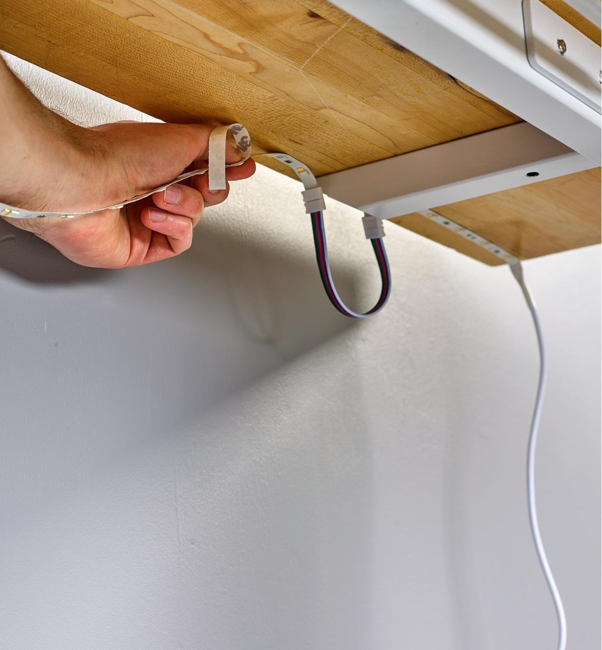 Personne installant un luminaire-ruban sous le plateau d'une table et contournant un tréteau à l'aide d'un câble connecteur