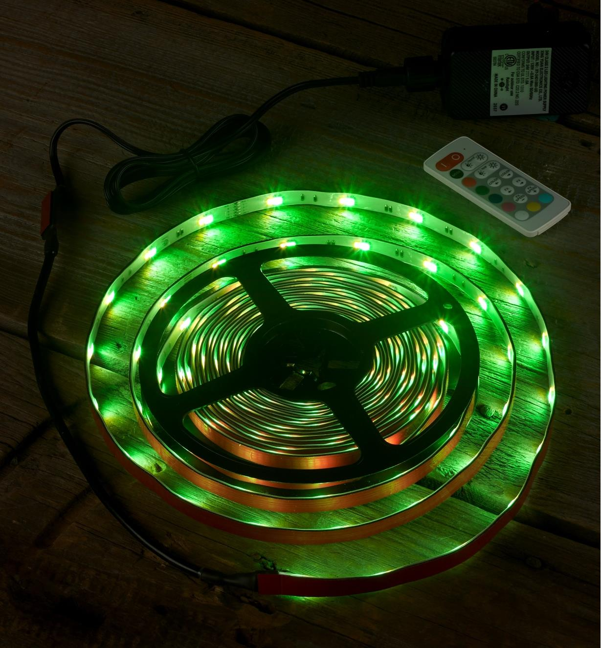 An LED color-controlled tape light kit set to a green hue to test it before installation