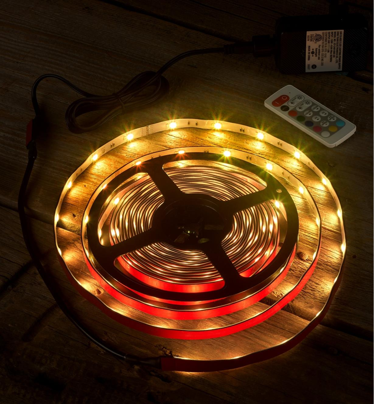 An LED color-controlled tape light kit set to a yellow hue to test it before installation