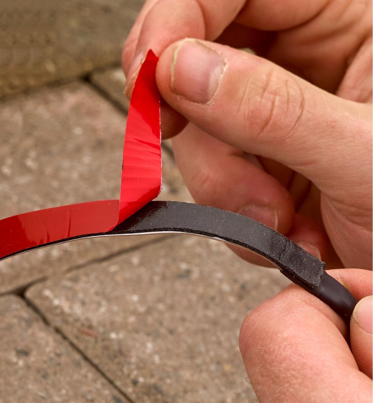Peeling the LED tape lighting's adhesive backing before mounting it
