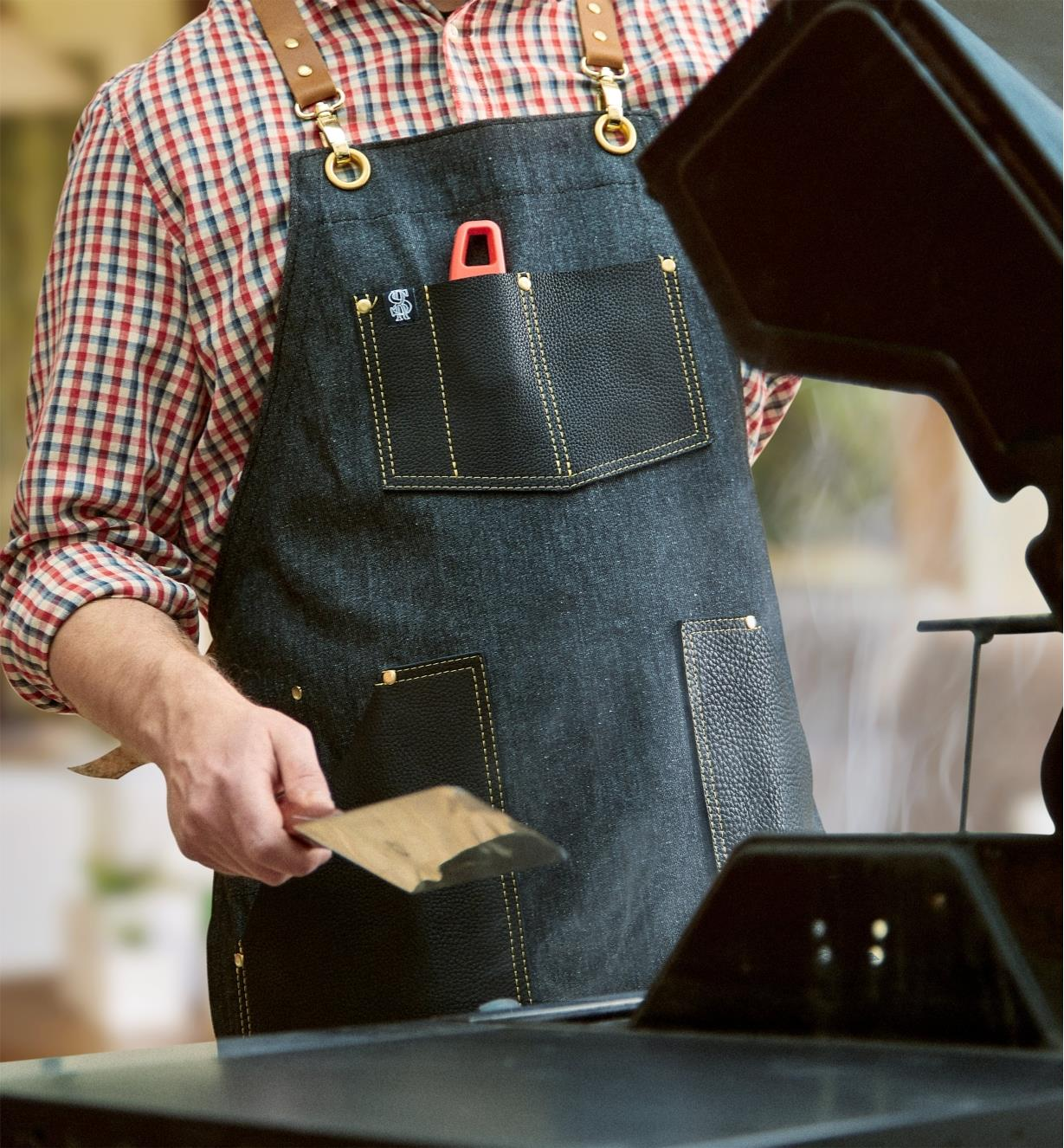 A man tending a barbecue in the All-Purpose Apron