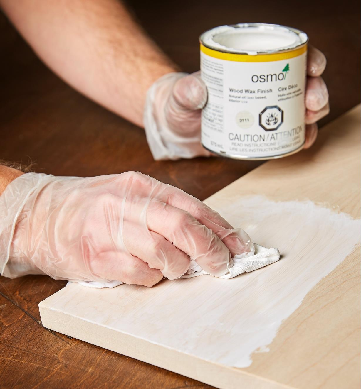 Using a cloth to apply Osmo white wood wax to a wood surface