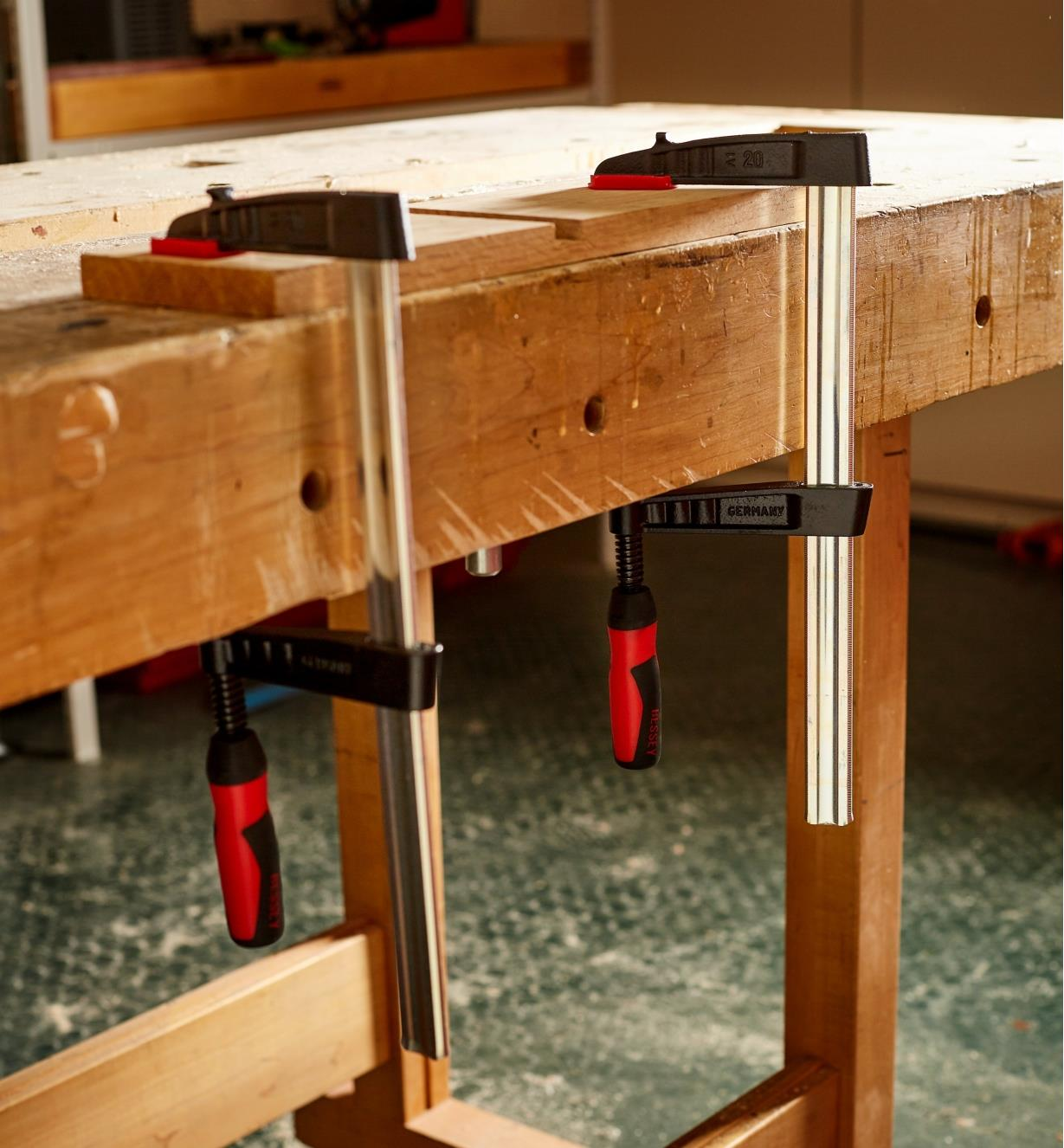 """Bessey 4"""" light-duty FA clamps used to clamp a piece of wood to a workbench"""