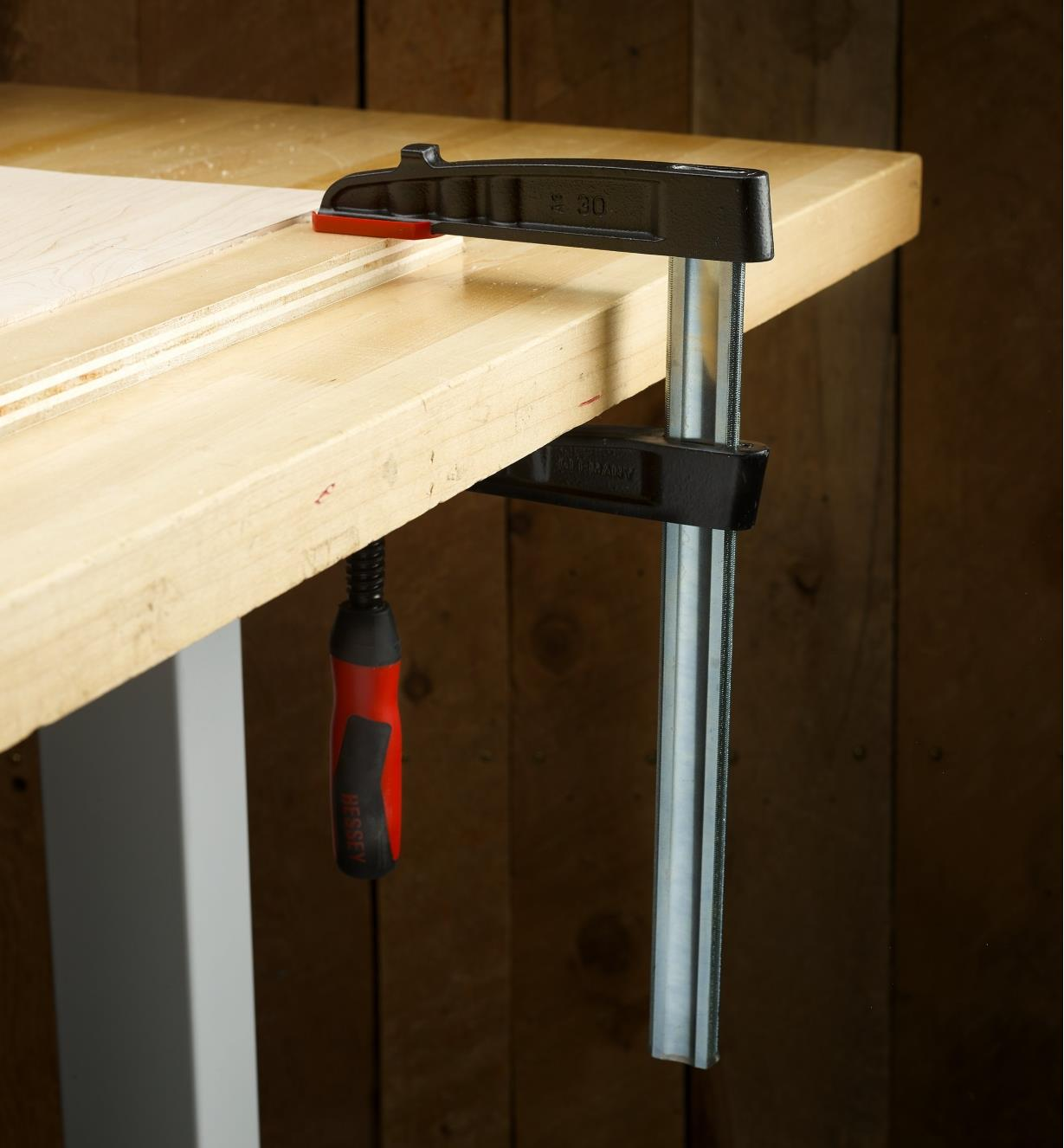 """A Bessey 5 1/2"""" medium-duty FA clamp clamping a piece of wood to a workbench"""