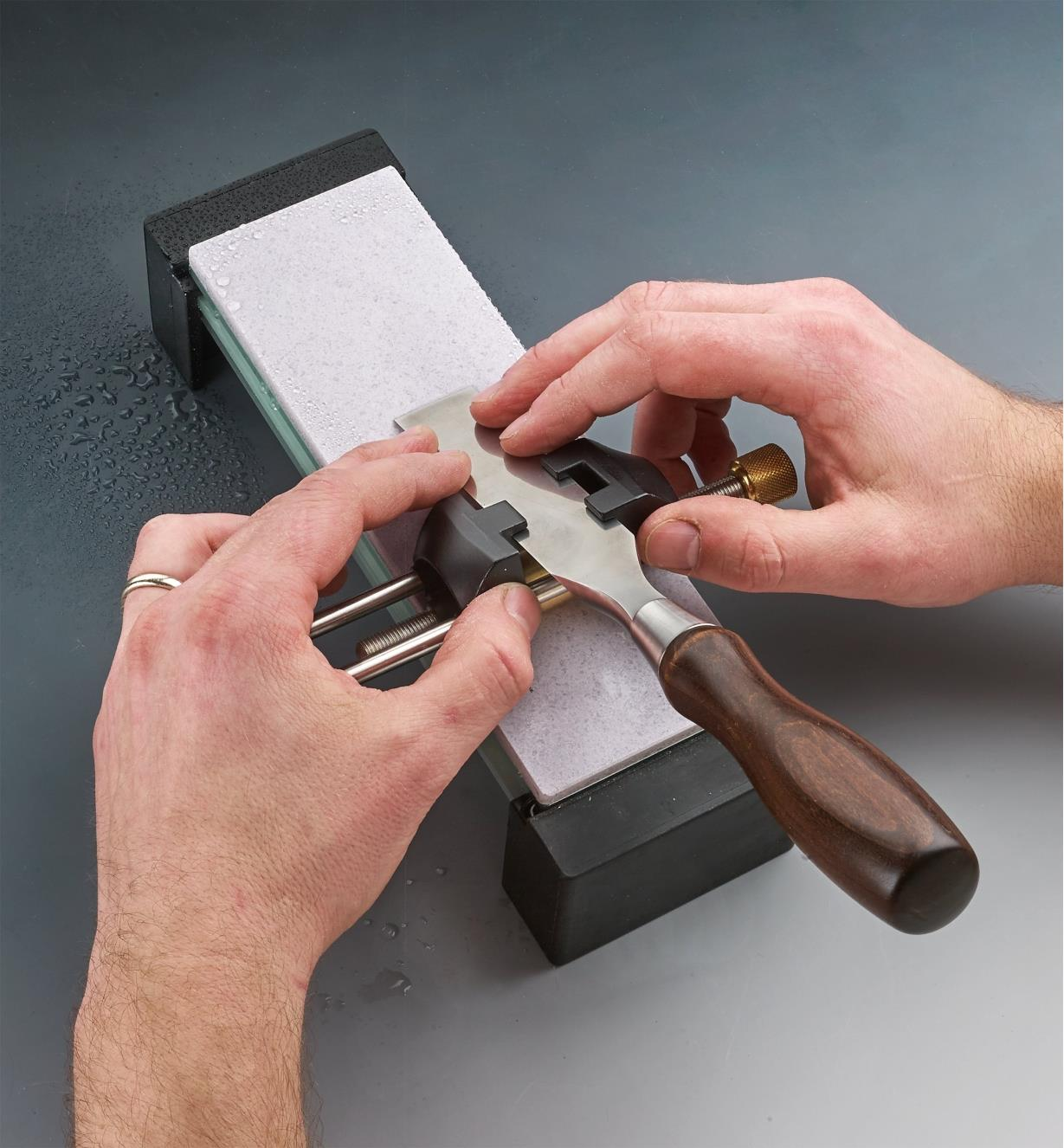 Sharpening a chisel on a glass stone held in a field holder
