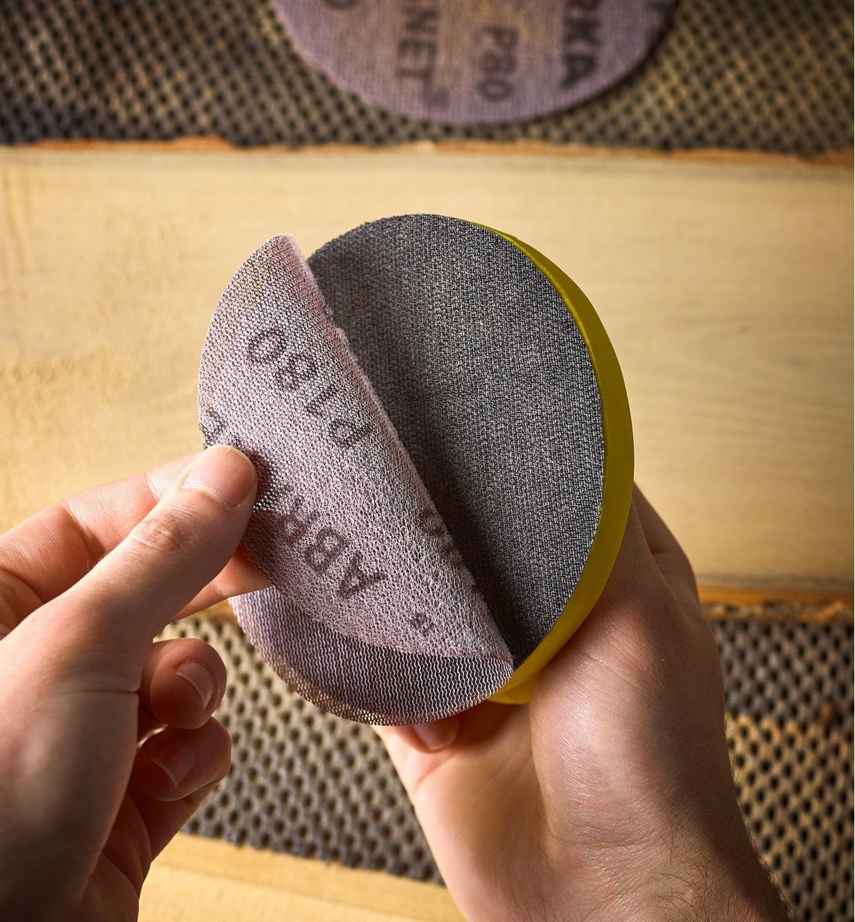 Personne posant un disque de ponçage sur une cale de ponçage de 5 po de diamètre
