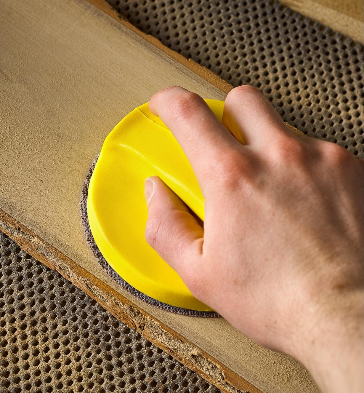 Personne ponçant une planche de bois à l'aide d'une cale de ponçage de 5 po de diamètre