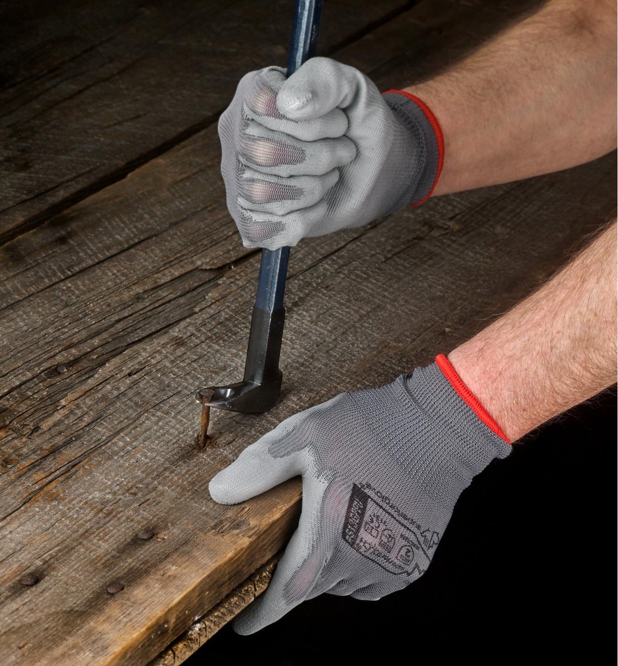 Personne portant des gants de travail légers pour retirer un clou d'une planche