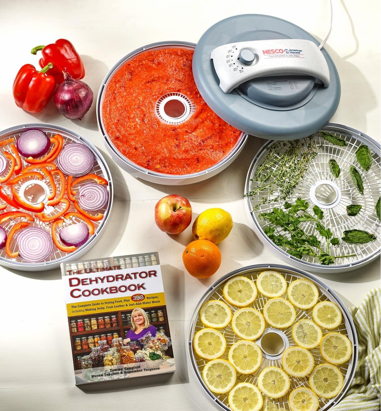 Le livre The Ultimate Dehydrator Cookbook posé près du déshydrateur alimentaire et de ses plateaux remplis d'aliments