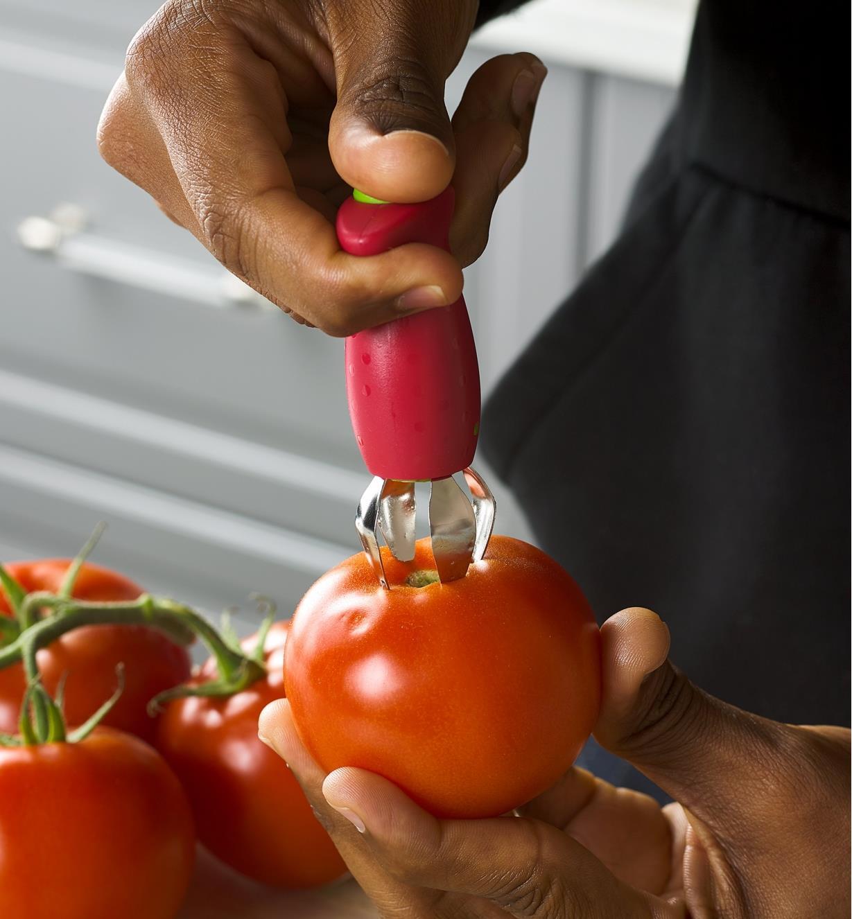 Personne appuyant sur le bouton de l'équeuteuse à fraises insérée dans une tomate pour en retirer la queue
