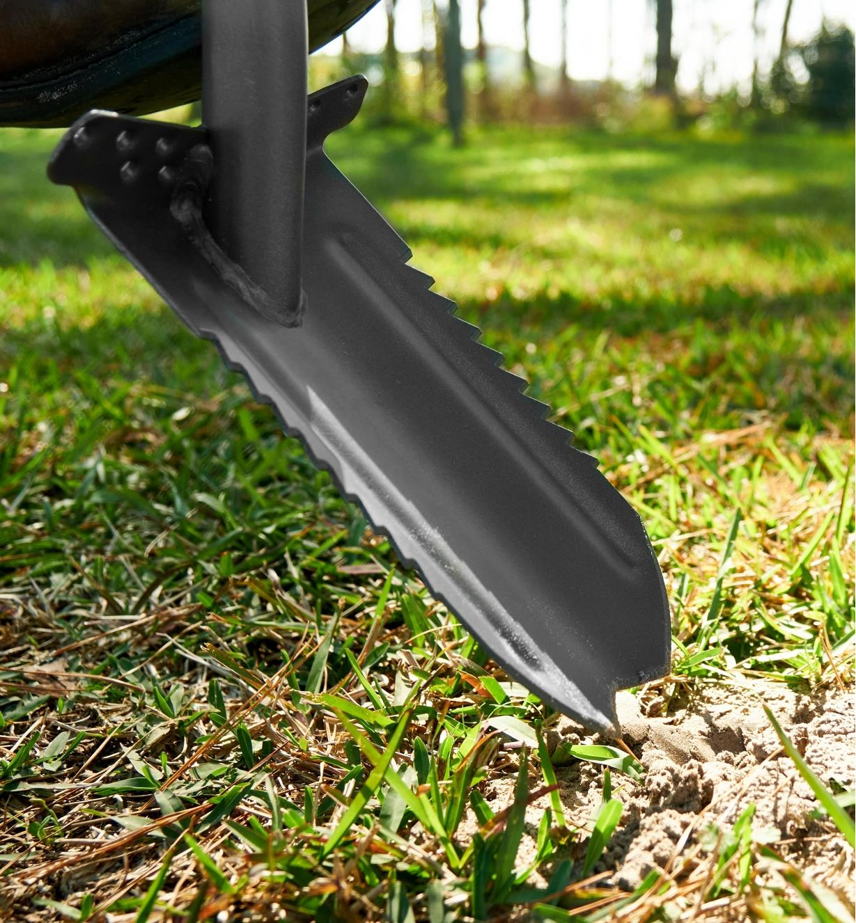 A close view of the root-cutter trenching spade's blade penetrating the soil