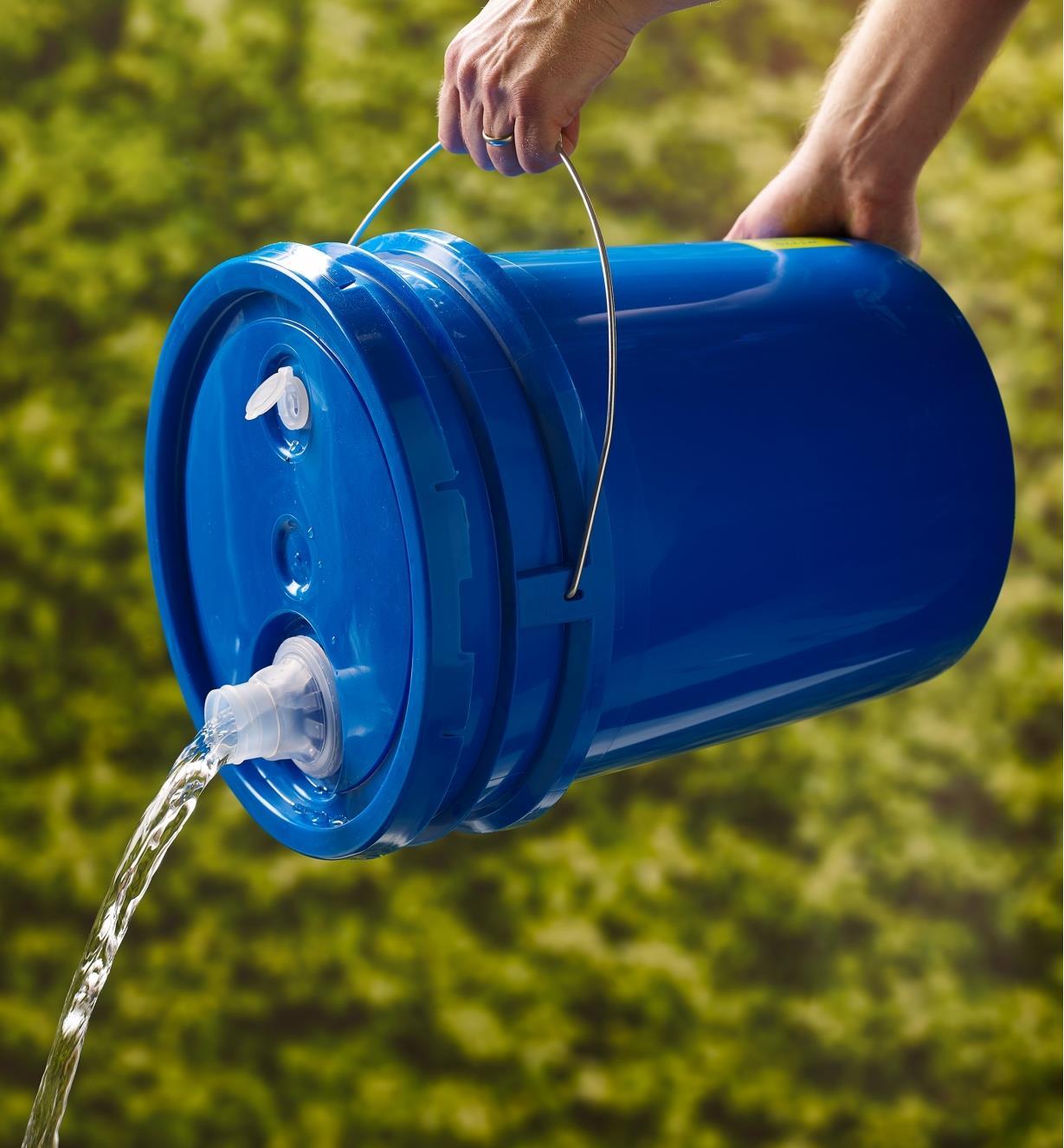 Personne versant de l'eau contenue dans un seau de 19 L Lee Valley à l'aide du bec verseur d'un couvercle à joint d'étanchéité