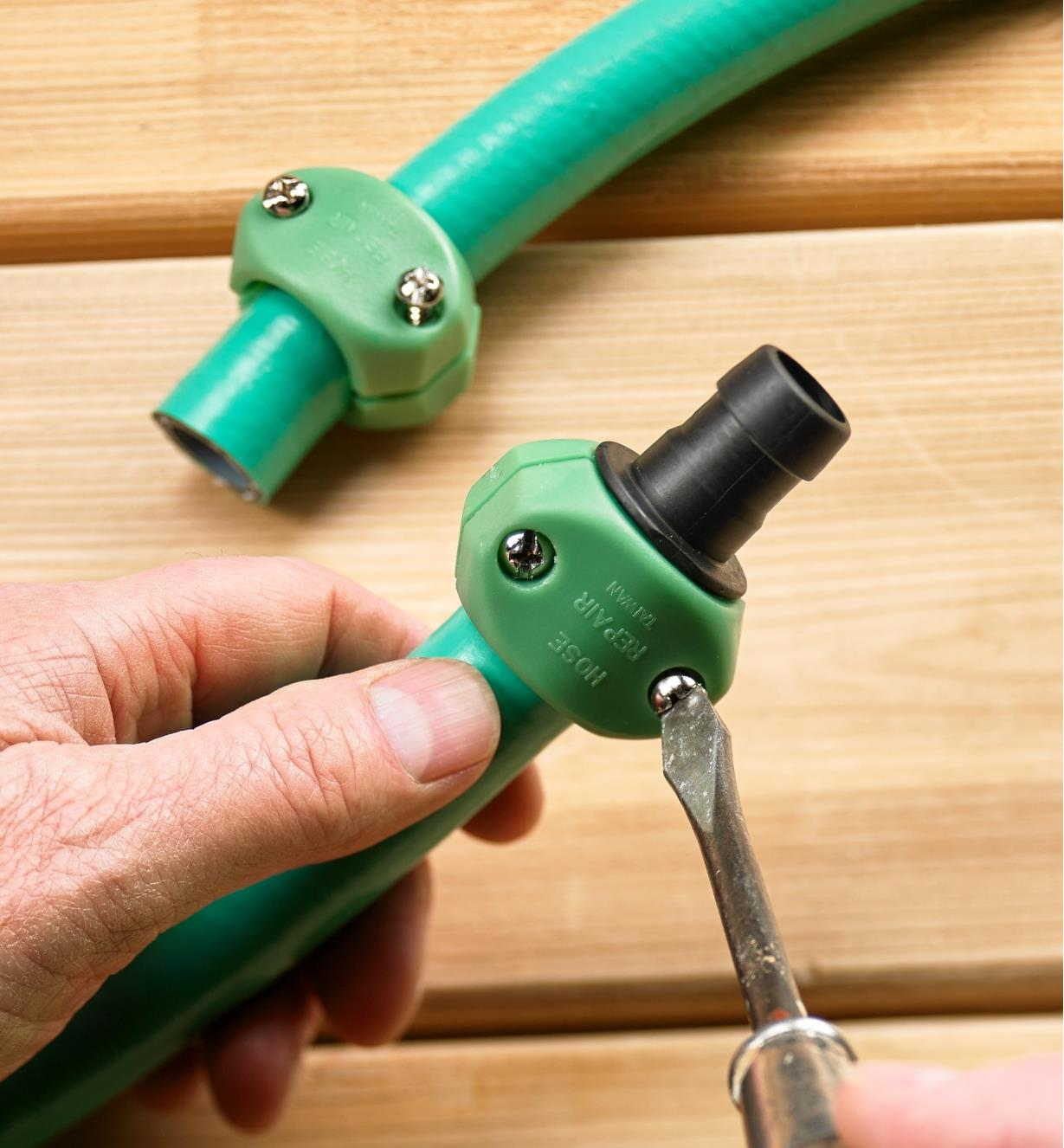 Attaching the hose mender to a section of garden hose using a screwdriver