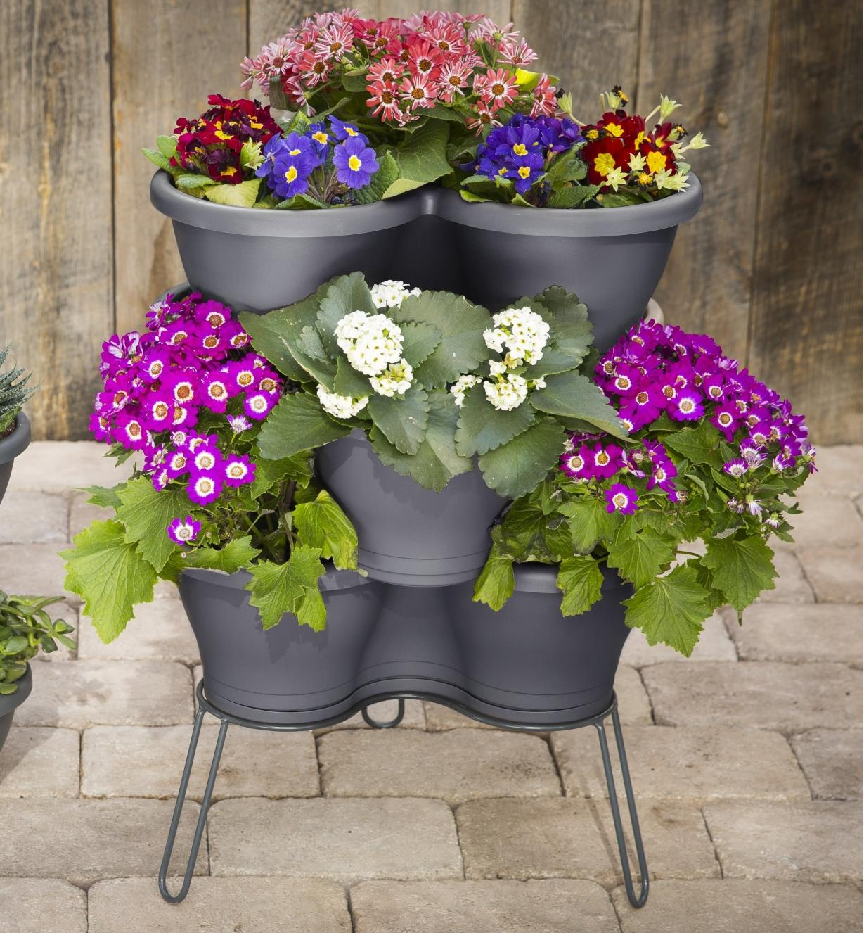 Stand supporting a flower planter with a catch tray