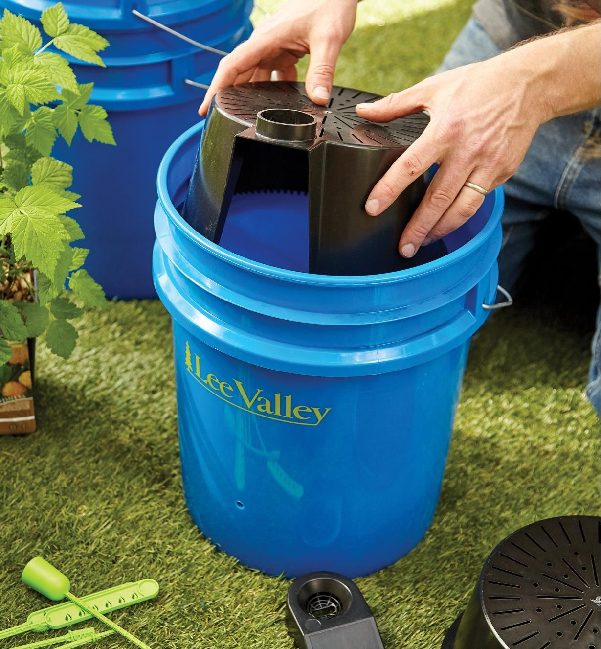 Lowering the reservoir of the GroBucket self-watering insert into a bucket