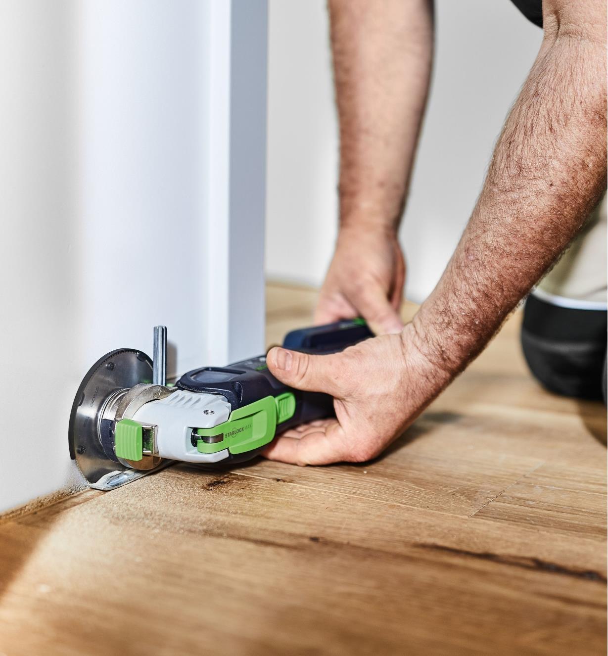 Personne effectuant une coupe en plongée dans un plancher en bois le long d'un mur avec un outil oscillant OSC 18 muni d'une lame pour bois