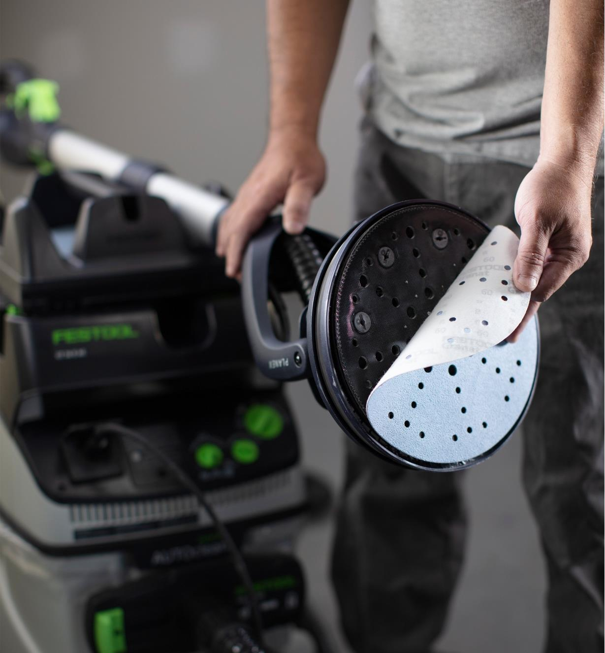 A piece of sandpaper is applied to the head of a Planex sander that is being held in place by the tool holder