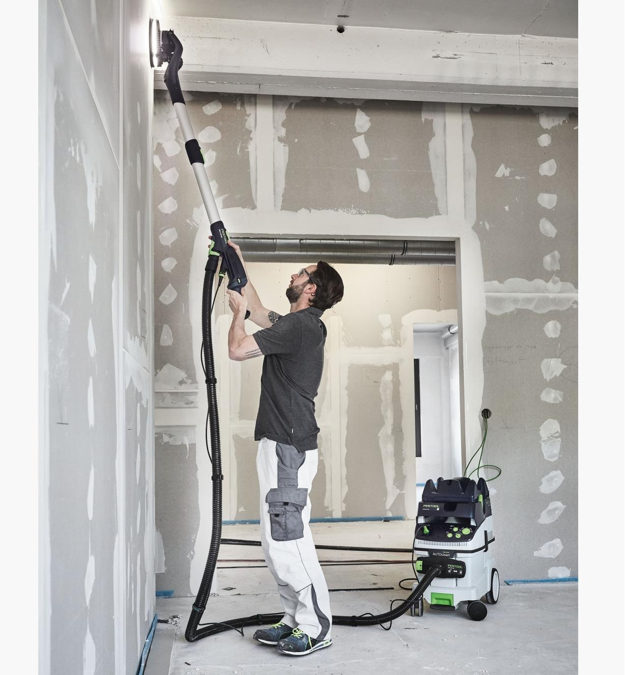 A worker sands the very top of a wall with the Planex LHS 2 225