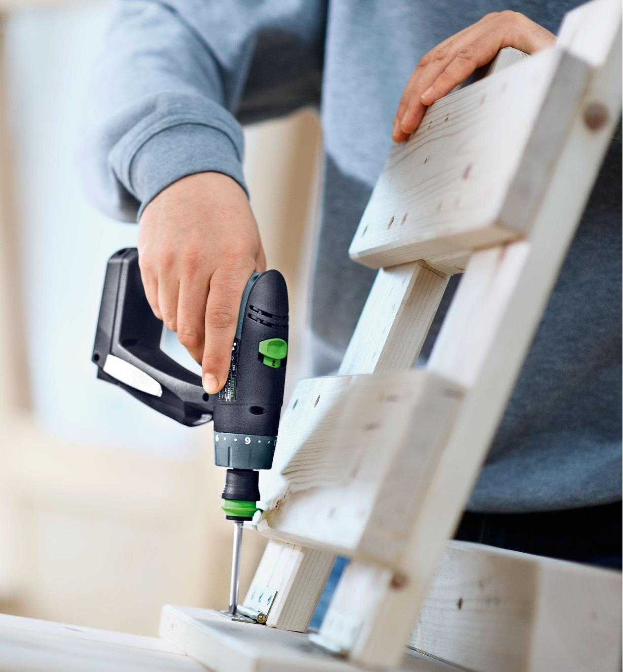Installing a hinge using a CXS Cordless Drill to secure the screws