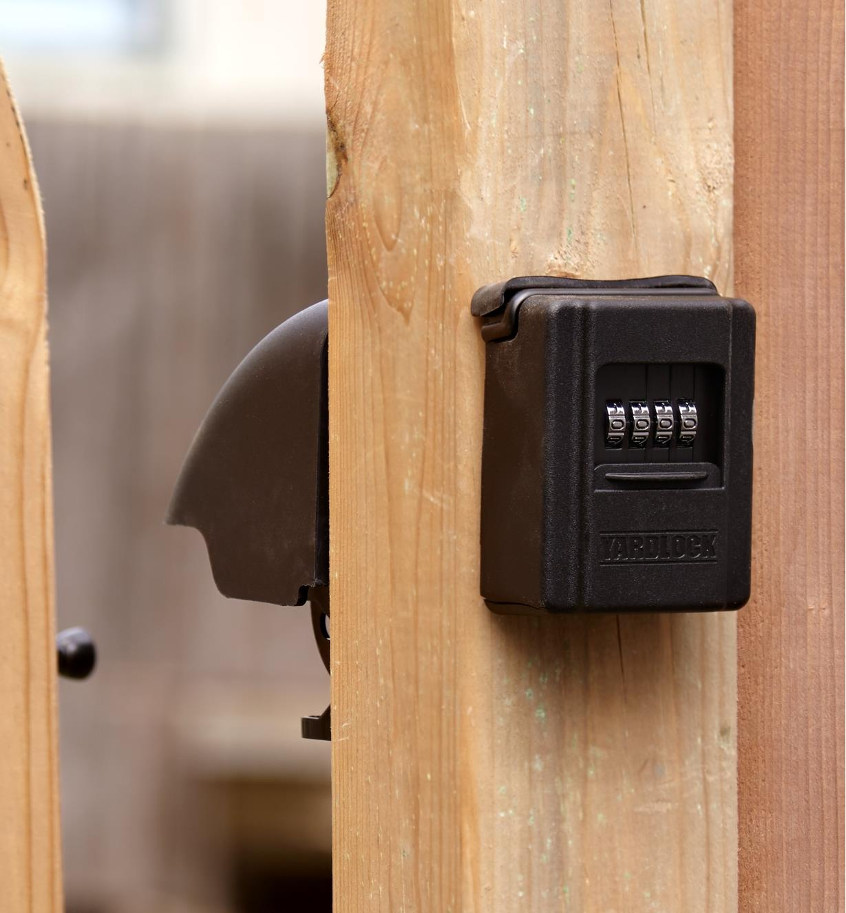 Keyless gate lock on street side of open gate with latch assembly partially visible