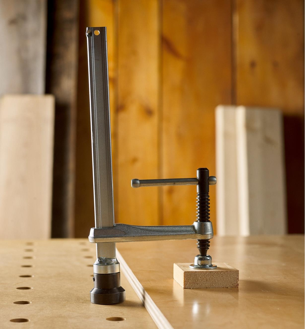 A Bessey hold-down clamp with a T-bar handle clamping veneer to a piece of plywood