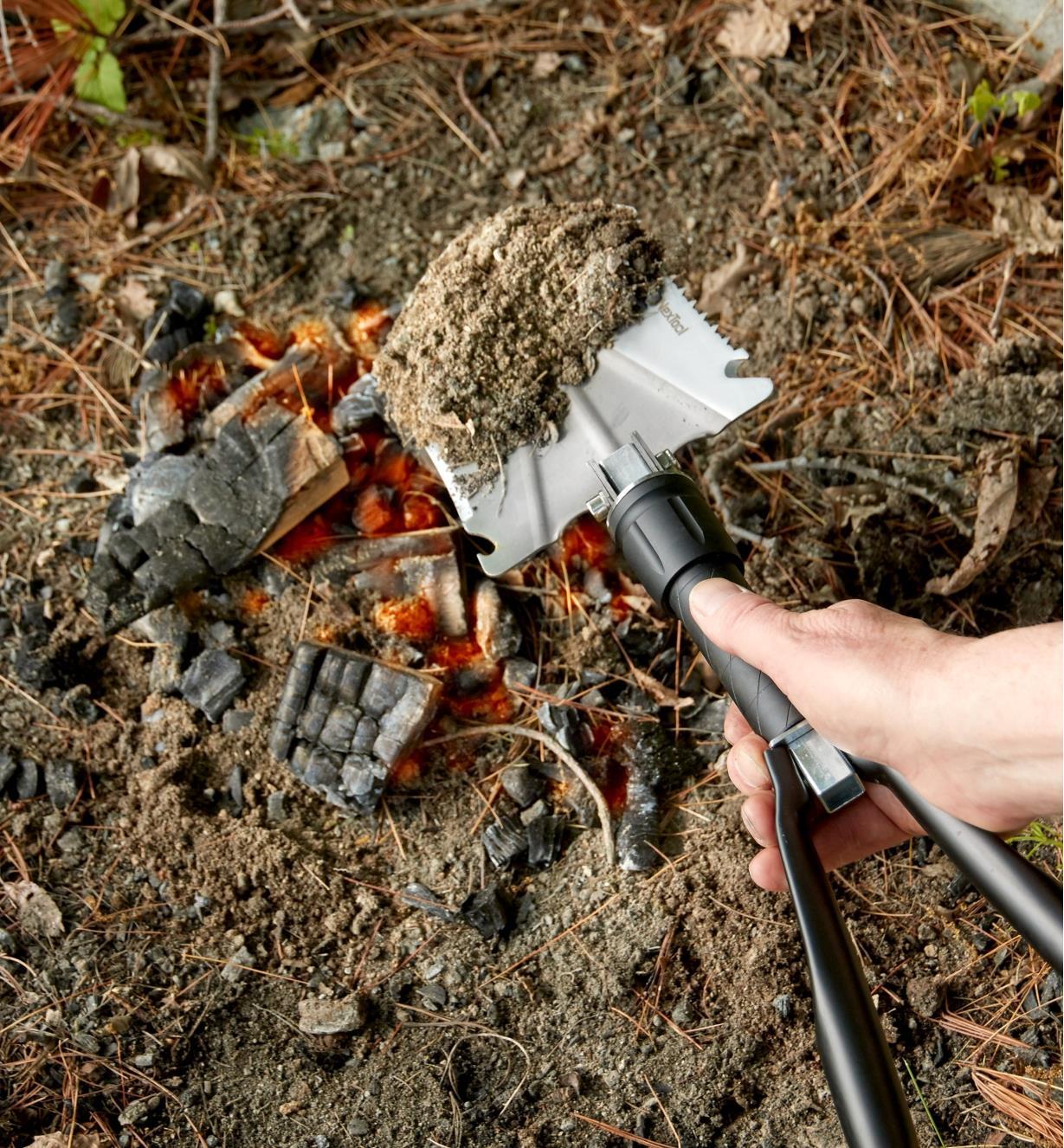 Personne utilisant la pelle pliante et éteignant un feu avec une pelletée de terre