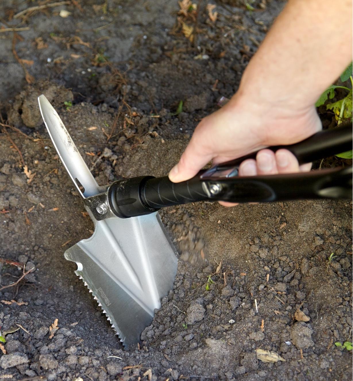Personne creusant à l'aide de la pelle pliante verrouillée à 90° par rapport au manche