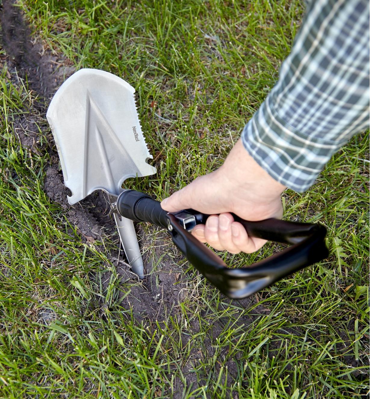 Personne creusant une tranchée à l'aide de la pioche sur la pelle pliante
