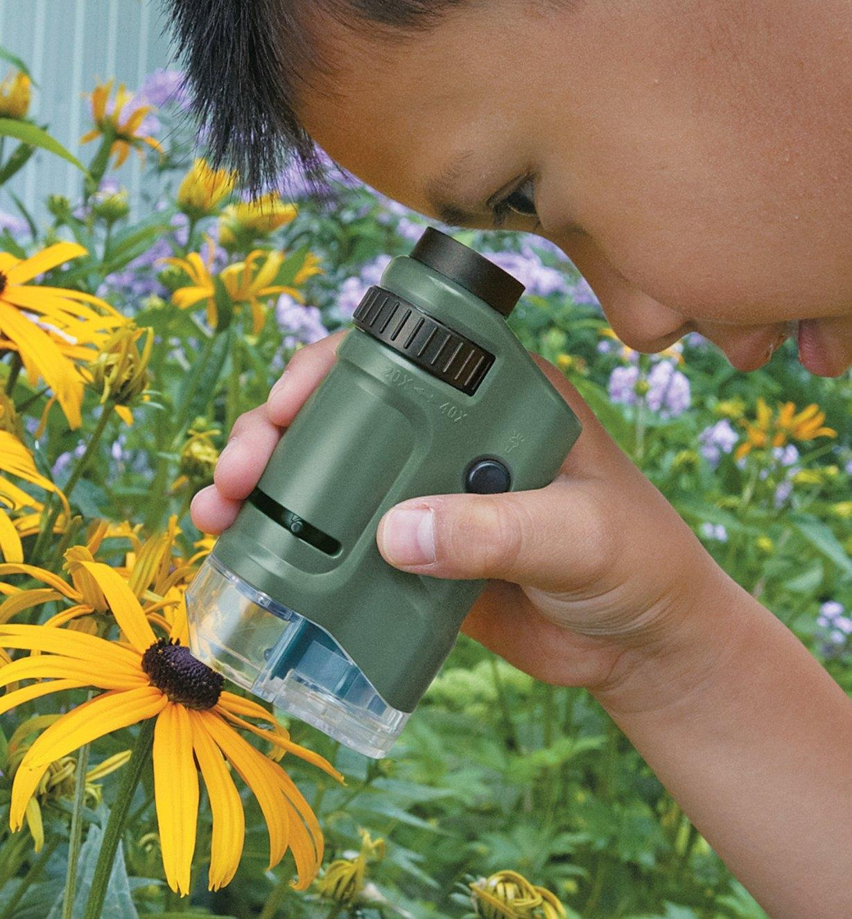 A child uses the Pocket Microscope to look at a flower