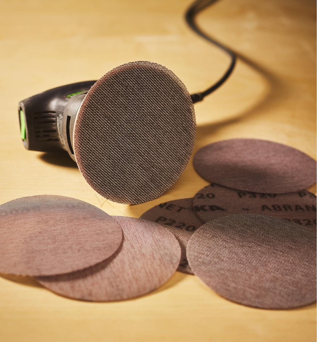"""A pile of Abranet 5"""" Sanding Discs beside an orbital sander with a sanding disc attached"""