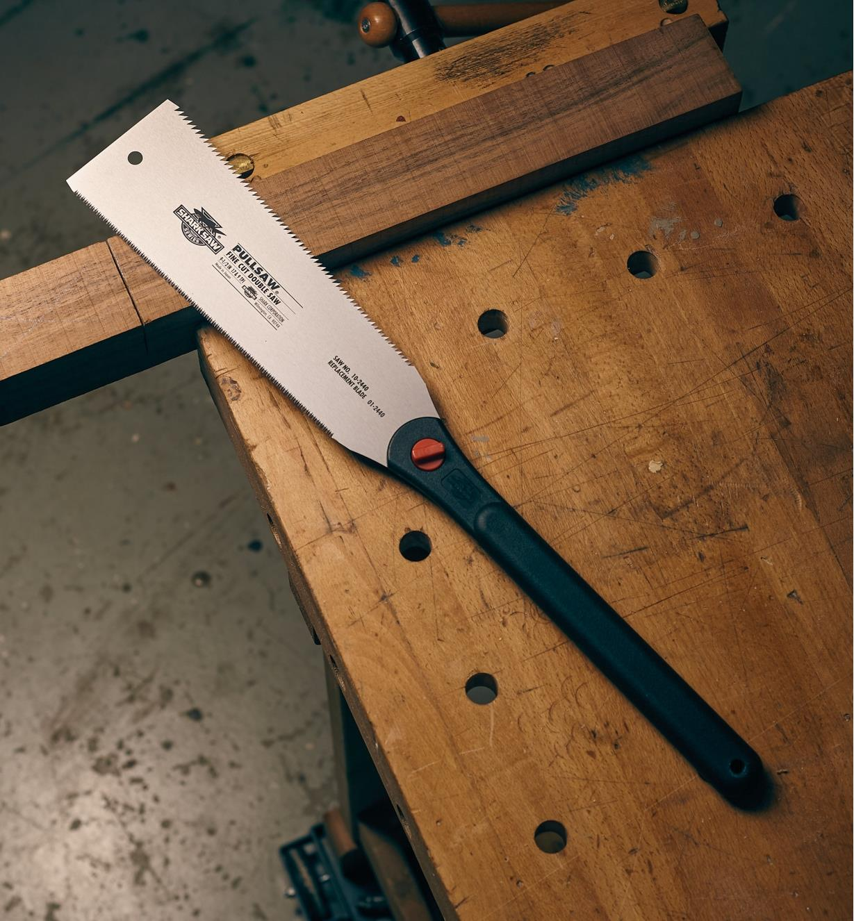 Side view of a Japanese modern ryoba saw lying on a workbench