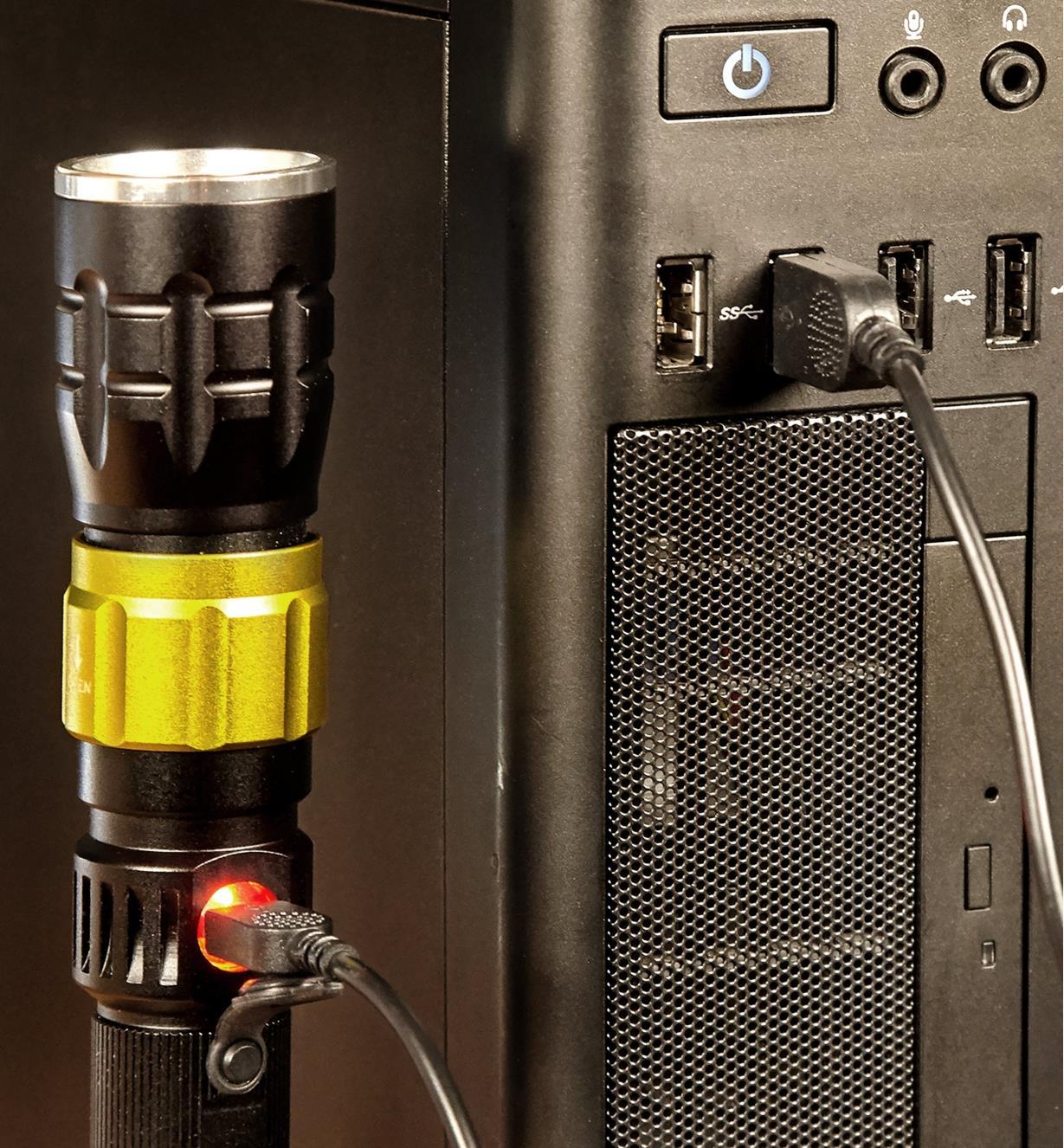 Lampe de travail 3-en-1 branchée à un ordinateur au moyen d'un câble USB pour en recharger la pile aux ions de lithium