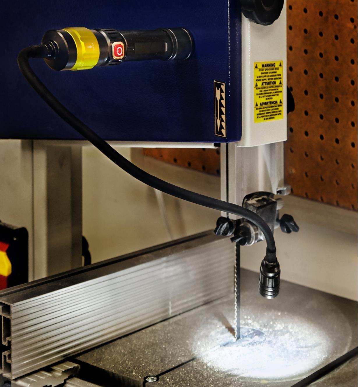 Base aimantée d'une lampe de travail 3-en-1 adhérant à une scie à ruban pour éclairer le plateau avec une lampe à bras flexible