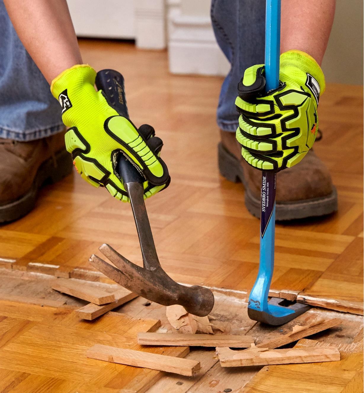 Personne munie de gants antichocs défaisant un plancher de bois franc au moyen d'un marteau et d'une barre à levier