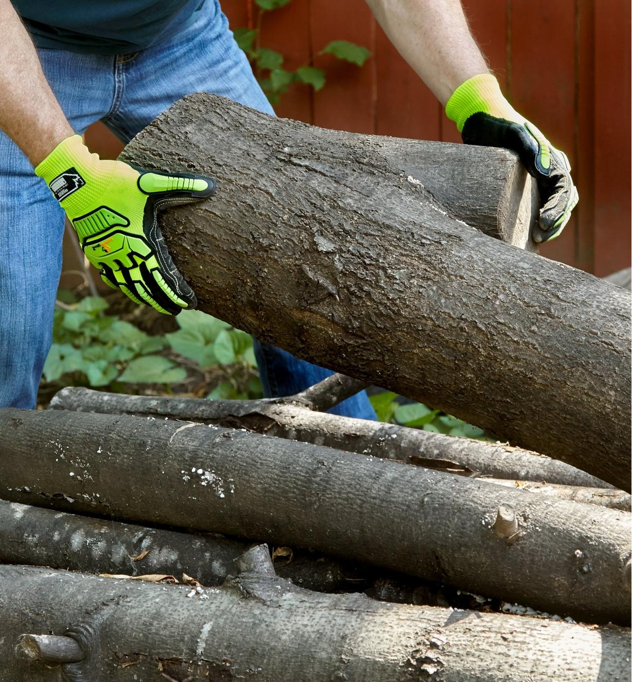A homeowner wears impact-resistant gloves while piling hardwood logs to be processed for firewood