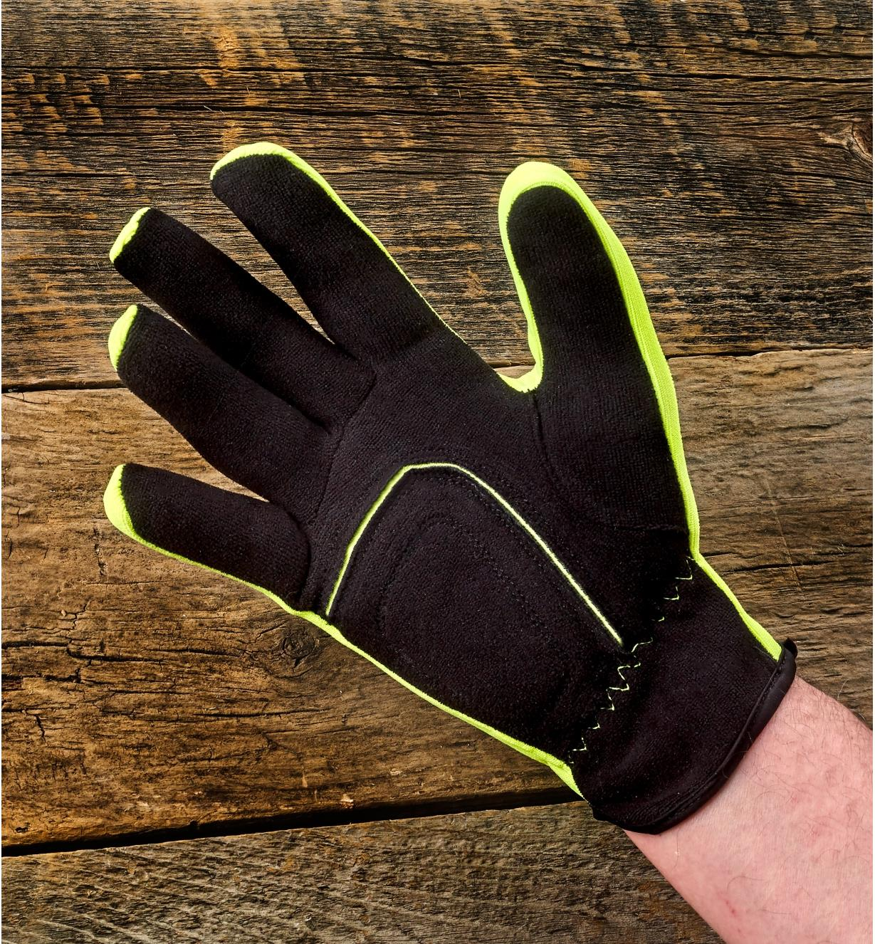 A yellow Universal-Fit glove being worn on a man's hand to show how it stretches for a snug fit