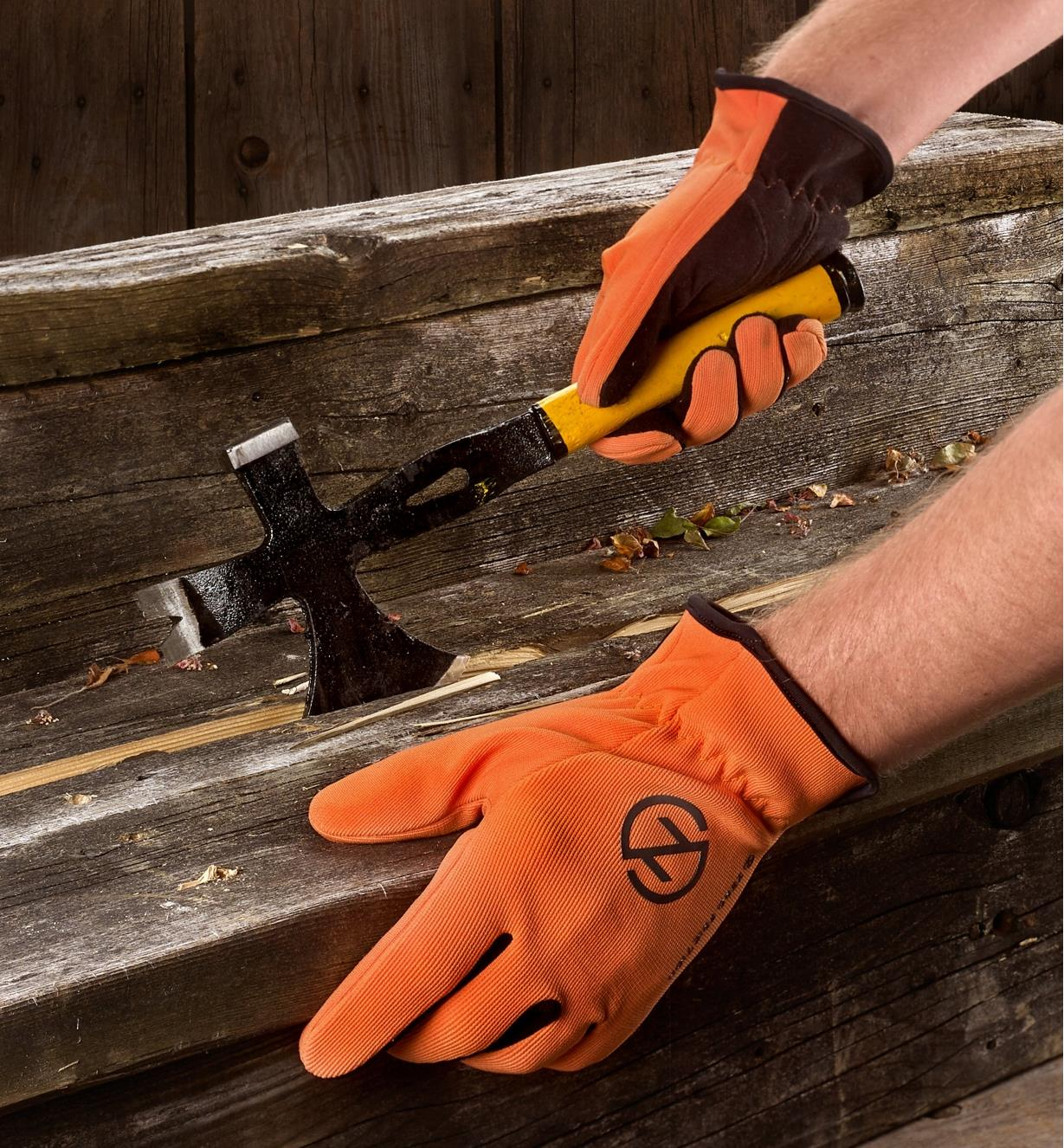 A person wears a pair of Universal-Fit gloves while dismantling an old set of wooden deck steps
