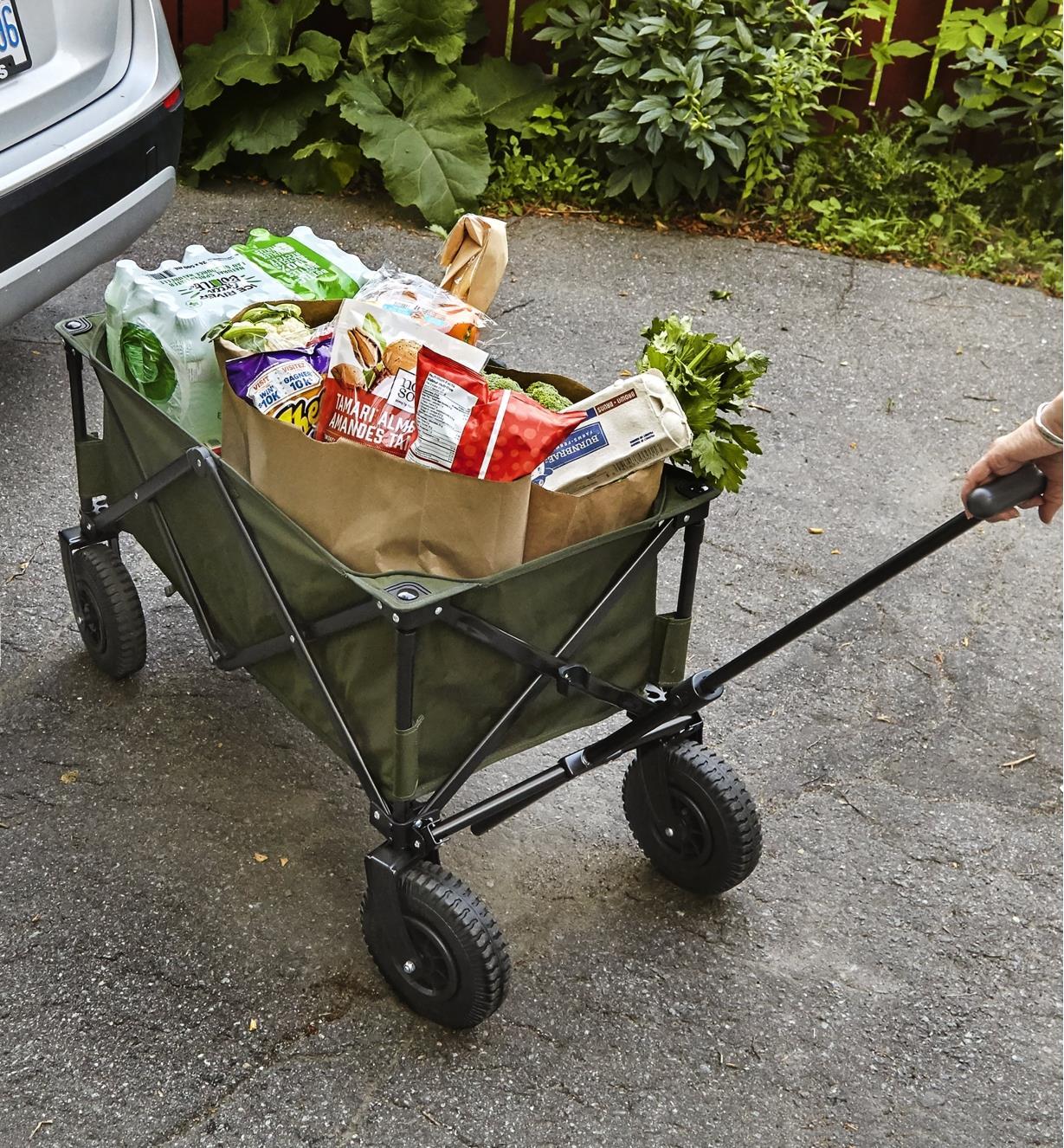 Personne tirant un chariot pliant rempli de sacs d'épicerie