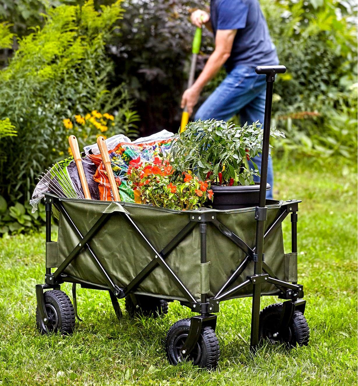 Un chariot pliant chargé de plantes, d'outils et de sacs de terreau dans un jardin