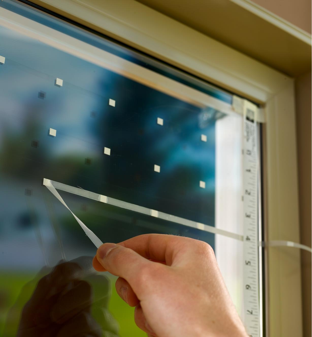Pulling translucent tape away from a row of white squares on a window