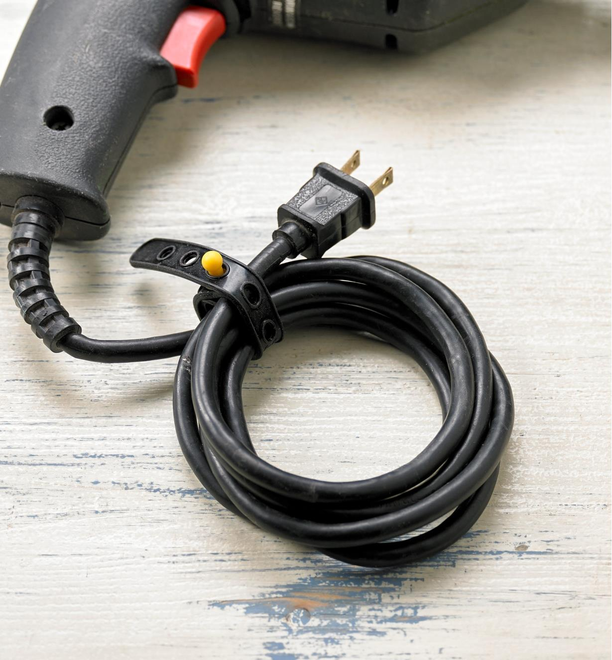 A tool electrical cord secured with a Wrap-N-Strap