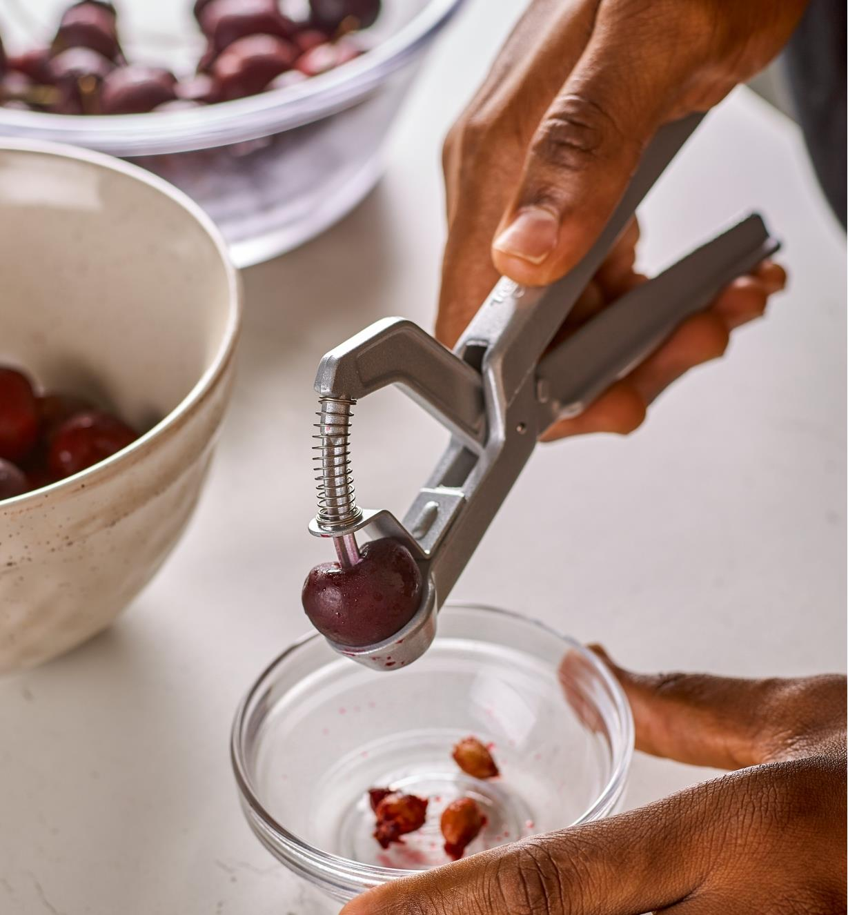 Squeezing the handles of the olive and cherry pitter