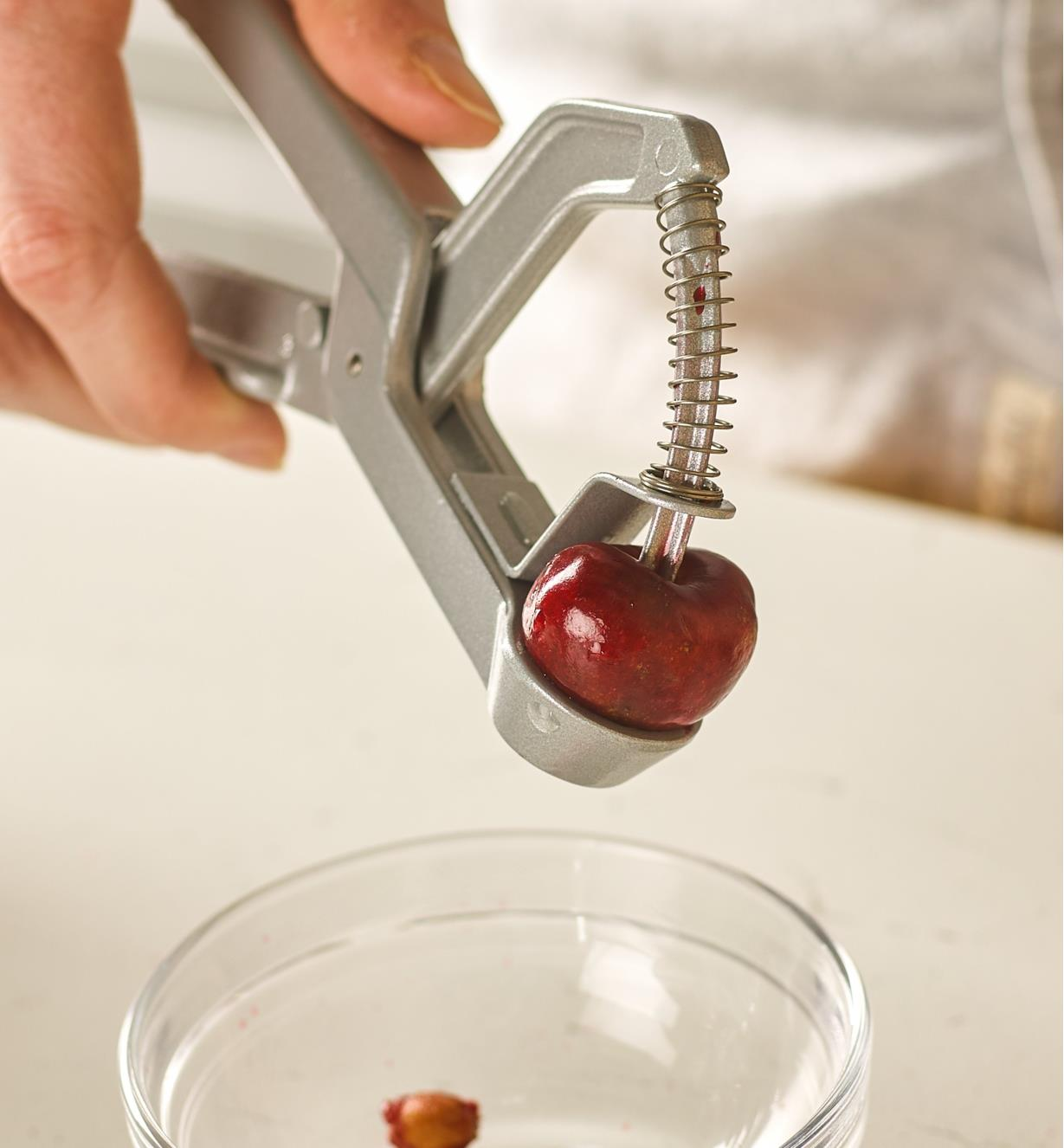 Spring-loaded plunger of the olive and cherry pitter pushes the pit through the fruit