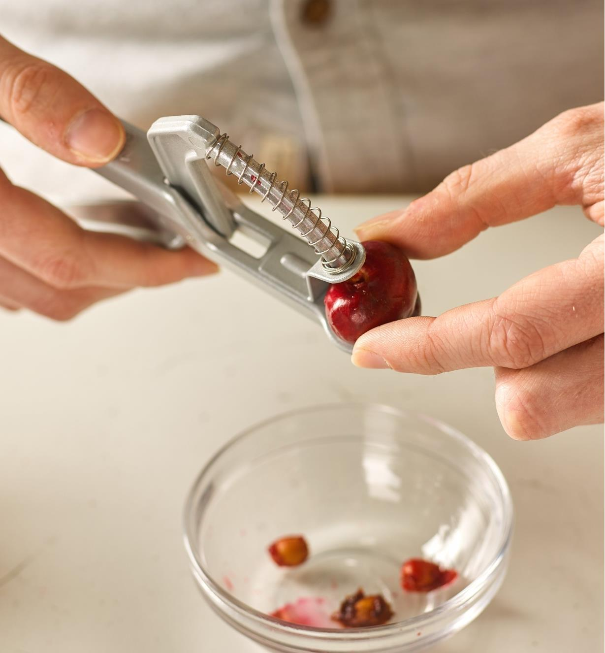 Removing the cherry from the olive and cherry pitter