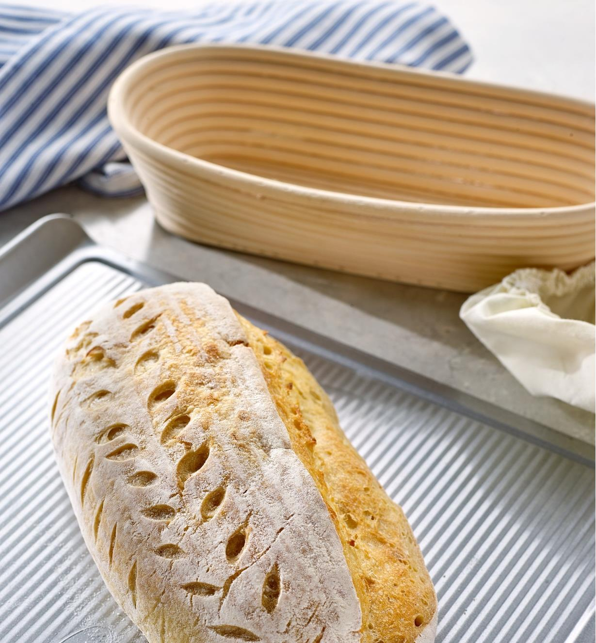 An oval bread is shown on a baking sheet next to an empty oval banneton