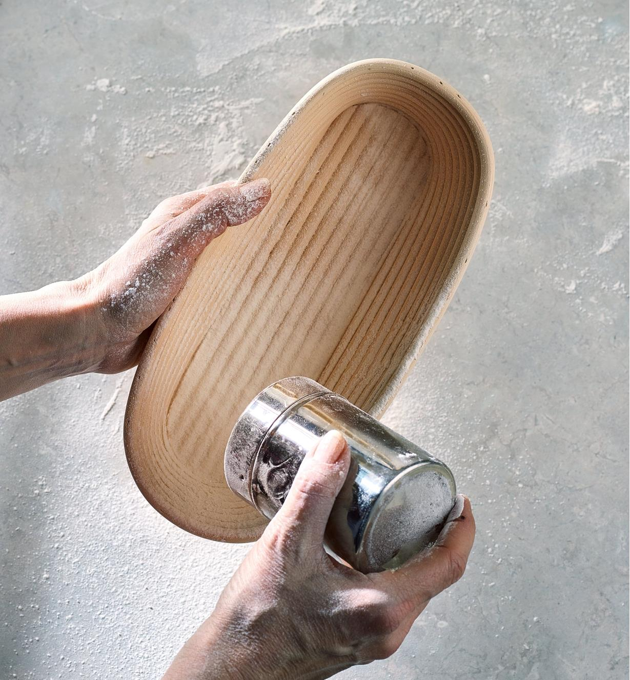 Using a stainless-steel flour shaker to dust the oval banneton with flour