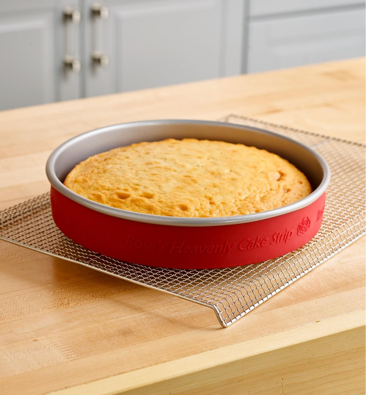 A cake baked in a pan fitted with a silicone cake strip rests on a cooling rack