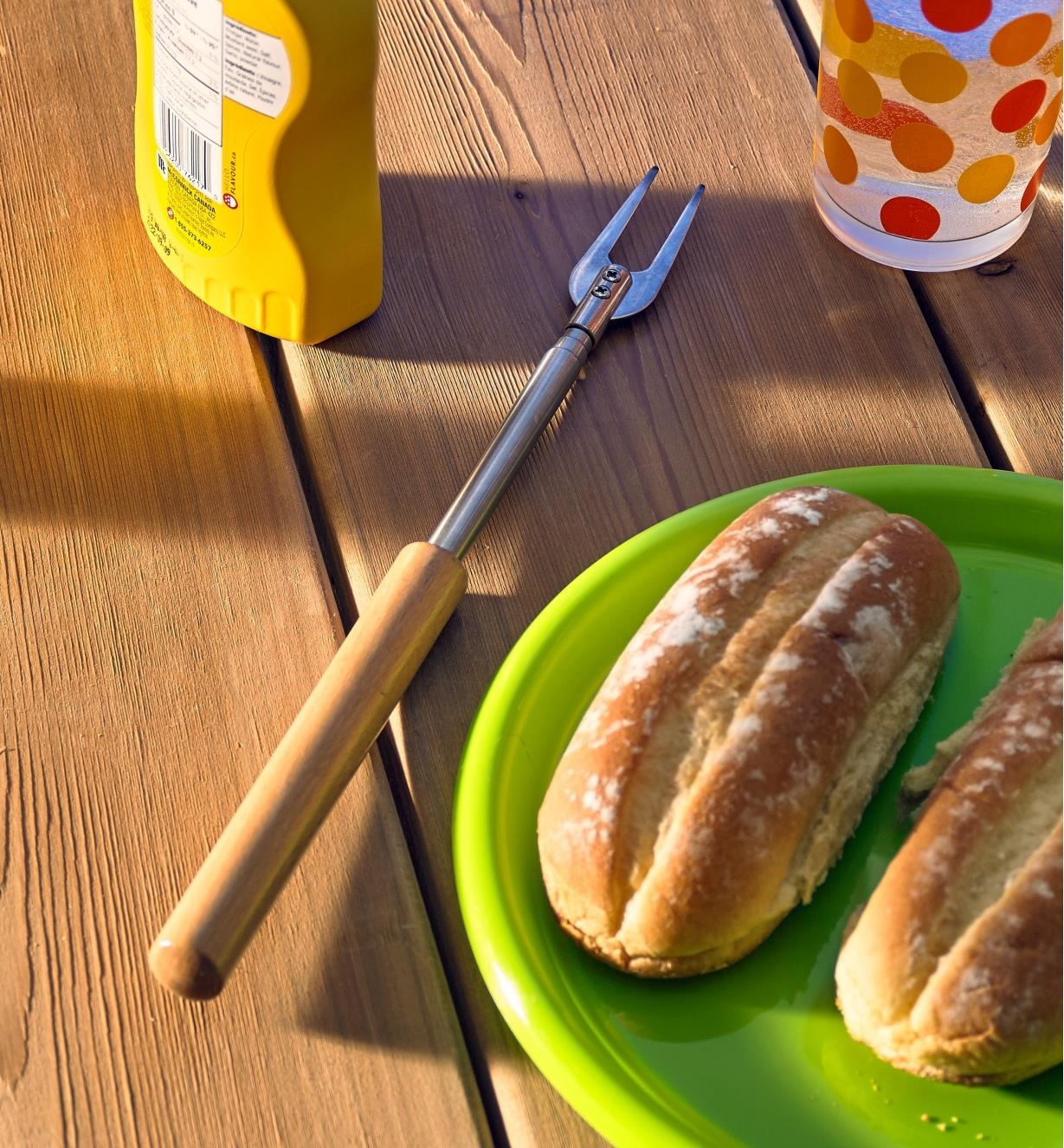 Telescoping campfire fork on a table with food items